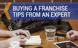 Two people exchanging information at table: Buying a Franchise Tips from TotSquad Founder/CEO