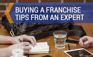 Two people sharing information at table: Buying a Franchise Tips from TotSquad Founder/CEO