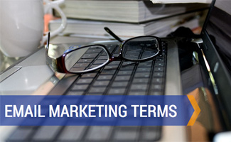 Laptop with book and glasses: Email Marketing Terms